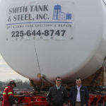 Image of people standing in front of a tank with Smith Tank  Steel logo on it.